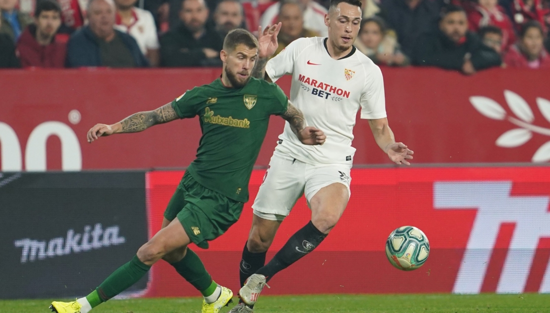 Ocampos battling for the ball with Íñigo Martínez